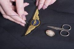 Das Nähen steuert Flügel auf Uniform Stockfotografie