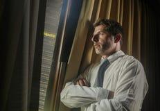 Das Nachtlicht-Büroporträt des Geschäftsmannes das späte Schauen bearbeitend sorgte sich durch das Fenster, das durchdacht sind u lizenzfreie stockfotos