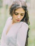 Das Nahaufnahmeporträt der Schönheit im weißen Hochzeitskleid, das den Boden im grünen Wald betrachtet Stockbilder