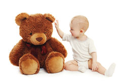 Das nette Baby, das mit großem Teddybären spielt, betreffen Weiß Stockfotos