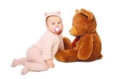 Das nette Baby, das mit großem Teddybären spielt, betreffen Weiß Lizenzfreie Stockfotografie