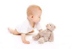 Das nette Baby, das mit Teddybären spielt, betreffen Weiß Lizenzfreies Stockbild