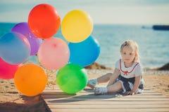 Das nette blonde Babykind, das aufwirft, Sommerlebenszeit auf Seite des sandigen Strandes Seeauf hölzernem Pier mit buntem viel g Stockbild