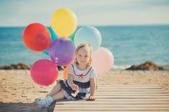 Das nette blonde Babykind, das aufwirft, Sommerlebenszeit auf Seite des sandigen Strandes Seeauf hölzernem Pier mit buntem viel g Lizenzfreie Stockbilder