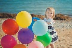 Das nette blonde Babykind, das aufwirft, Sommerlebenszeit auf Seite des sandigen Strandes Seeauf hölzernem Pier mit buntem viel g Lizenzfreies Stockbild
