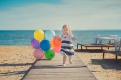 Das nette blonde Babykind, das aufwirft, Sommerlebenszeit auf Seite des sandigen Strandes Seeauf hölzernem Pier mit buntem viel g Stockfotos