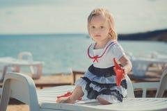 Das nette blonde Babykind, das aufwirft, Sommerlebenszeit auf Seite des sandigen Strandes Seeauf hölzernem Pier mit buntem viel g Lizenzfreie Stockfotografie