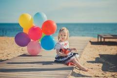 Das nette blonde Babykind, das aufwirft, Sommerlebenszeit auf Seite des sandigen Strandes Seeauf hölzernem Pier mit buntem viel g Stockfotografie