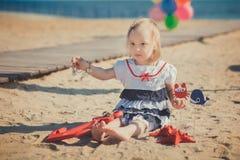 Das nette blonde Babykind, das aufwirft, Sommerlebenszeit auf Seite des sandigen Strandes Seeauf hölzernem Pier mit buntem viel g Lizenzfreie Stockfotos