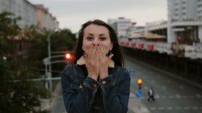 Das nette, glückliche, lächelnde Mädchen, das auf der Brücke steht, sendet Küsse, haben Spaß, Blicke auf die Kamera 4K Lizenzfreies Stockbild