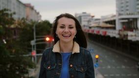 Das nette, glückliche, lächelnde Mädchen, das auf der Brücke steht, sendet Küsse, haben Spaß, Blicke auf die Kamera 4K Stockfoto