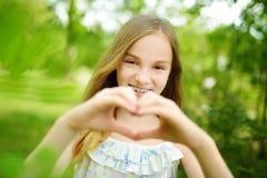 Das nette jugendliche Mädchen, das ihre Hände in einem Herzen lacht und hält, formen am hellen und sonnigen Sommertag Nettes Kind lizenzfreies stockfoto