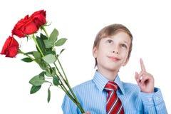 Das nette junge liebevolle Kind, das ein Hemd und eine Bindung halten Rosen whearing ist, hat eine Geschenkidee Stockfotos
