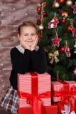 Das nette köstliche Mädchen, welches die stilvolle zufällige Kleidung glücklich ist trägt, genießen Weihnachtszeitfeiertage nah a stockbild