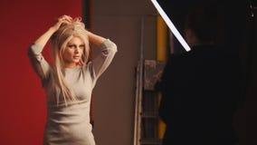 Das nette kaukasische blonde weibliche Modell, das für Fotografen aufwirft - arbeiten Sie Bühne hinter dem Vorhang um Stockbild