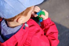 Das nette kaukasische Kind, das handgemachtes Spielzeug spielt, nannte Schlamm Lizenzfreie Stockfotografie