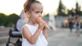 Das nette kaukasische kleine Mädchen genießt Eiscreme in einem Waffelkegel gehend in den Park Das Kind isst helle Eiscreme stock footage