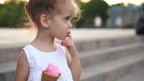 Das nette kaukasische kleine Mädchen genießt Eiscreme in einem Waffelkegel gehend in den Park Das Kind isst helle Eiscreme stock video footage