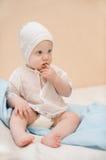Das nette Kind, das im Weiß gekleidet wird, sitzt auf dem Bett thinki Lizenzfreie Stockfotos