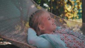 Das nette Kindermädchen, das auf Hängematte liegt und entspannen sich am Garten stock footage