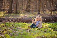 Das nette Kindermädchen, das im Grün sitzt, verlässt im Vorfrühlingswald Lizenzfreie Stockfotografie