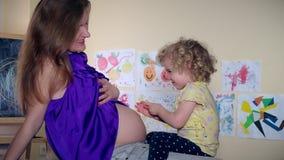 Das nette Kindermädchenküssen kitzeln und umarmen ihre Mutter der schwangeren Frau, die Bauch auf Sofa sitzen stock video