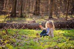 Das nette Kindermädchen, das im Grün sitzt, verlässt im Vorfrühlingswald Lizenzfreies Stockbild