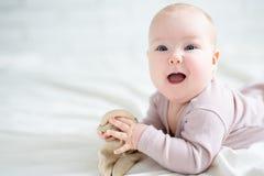 Das nette kleine Baby, das auf dem Bett mit Spielzeug liegen und die Kopie sperren O Stockbilder