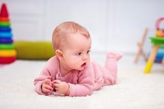 Das nette kleine Baby, das auf den Teppich unter der Entwicklung kriecht, spielt Stockfotografie