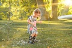 Das nette kleine blonde Mädchen in den Gummistiefeln, die mit Wasser spielen, spritzt auf dem Feld im Sommer Stockfoto