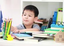 Das nette kleine Kind, welches die Hausarbeit liest einen Buchfarbton tut, paginiert w Lizenzfreie Stockfotos
