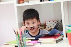 Das nette kleine Kind, welches die Hausarbeit liest einen Buchfarbton tut, paginiert w Stockbilder