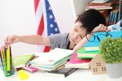Das nette kleine Kind, welches die Hausarbeit liest einen Buchfarbton tut, paginiert w Lizenzfreie Stockbilder
