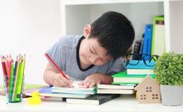 Das nette kleine Kind, welches die Hausarbeit liest einen Buchfarbton tut, paginiert w Stockbild