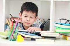 Das nette kleine Kind, welches die Hausarbeit liest einen Buchfarbton tut, paginiert w Stockfotografie