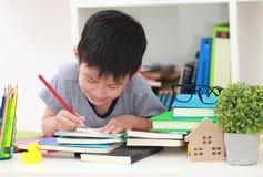 Das nette kleine Kind, welches die Hausarbeit liest einen Buchfarbton tut, paginiert w Lizenzfreies Stockfoto