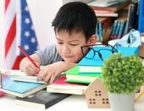Das nette kleine Kind, welches die Hausarbeit liest einen Buchfarbton tut, paginiert w Stockfotos