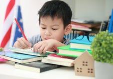 Das nette kleine Kind, welches die Hausarbeit liest einen Buchfarbton tut, paginiert w Stockfoto