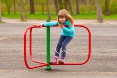 Das nette kleine Mädchen, das auf fröhlichem spielt, gehen Umlauf Lizenzfreies Stockfoto