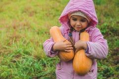 Das nette kleine Mädchen draußen spielen, das einen Kürbis hält Ernte von Kürbisen, Herbst im Garten, das reizende Mädchen und gr lizenzfreie stockbilder