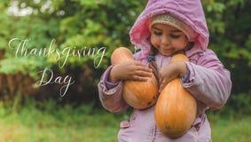 Das nette kleine Mädchen draußen spielen, das einen Kürbis hält Ernte von Kürbisen, von reizenden Mädchen und von großen Kürbisen stockfotografie