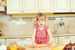 Das nette kleine Mädchen, das ihrer Mutter hilft, backen Plätzchen in einer Küche Lizenzfreie Stockfotos