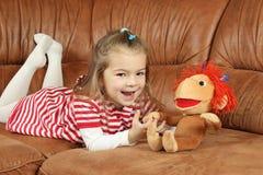 Das nette kleine Mädchen mit einem weichen Spielzeug - der Affe Lizenzfreie Stockbilder