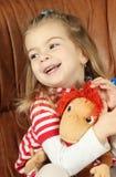 Das nette kleine Mädchen mit einem weichen Spielzeug - der Affe Lizenzfreies Stockbild