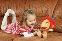 Das nette kleine Mädchen mit einem weichen Spielzeug - der Affe Lizenzfreie Stockfotografie