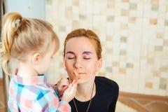 Das nette kleine Mädchen, das mit Mama ` s spielt, bilden Lizenzfreies Stockfoto