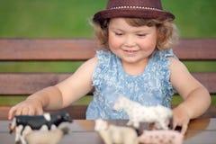 Das nette kleine Mädchen, das mit Vieh spielt, spielt draußen Stockfoto
