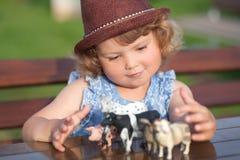Das nette kleine Mädchen, das mit Vieh spielt, spielt draußen Lizenzfreies Stockfoto