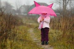 Das nette kleine Mädchen unter einem Regenschirm im Fall Stockfoto