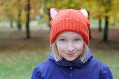 Das nette lächelnde Mädchen, das Kind wird in einem lustigen gestrickten warmen Hut mit den Ohren, aussieht wie ein Fuchs gekleid Stockfoto